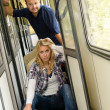 Woman and man sitting on train hallway - Stock Photo