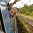 Couple waving with heads out train window — Stock Photo #17418075
