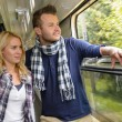 Couple looking out the train window smiling — Stock Photo #17418099