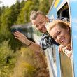 Couple waving with heads out train window - Stock Photo