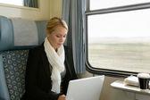 Kobieta korzysta z laptopa, podróżując pociągiem podmiejskim — Zdjęcie stockowe