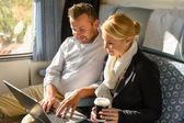 Woman and man relaxing in train laptop — Stock Photo