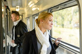Woman looking out the train window traveling — Stock Photo