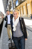 Woman in train station man on cellphone — Stock Photo