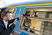 Man saying goodbye to woman on train — Stockfoto