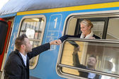 Woman leaving with train man holding hand — Stockfoto