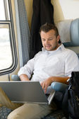 Man sitting in train using laptop computer — Stock Photo