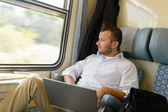 Man looking out the train window laptop — Stock Photo
