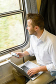 Man looking out the train window thinking — Stockfoto