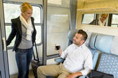 Woman getting in train compartment with man — Stock Photo