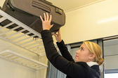 Woman putting her luggage on train rack — Stock Photo
