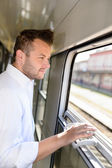 Man looking out the train window smiling — Stockfoto