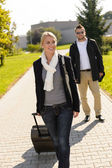 Woman leaving with baggage man walk behind — Stockfoto