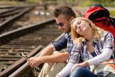 Couple backpack traveling resting on railroad map — Stock Photo