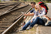 Couple resting looking at map railroad backpack — Stock Photo