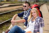 Couple backpack traveling resting on railroad trip — Stock Photo