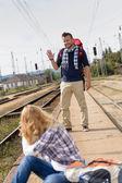 Homem acenando a mulher sentada na ferrovia — Fotografia Stock