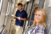 Woman smiling and man reading in train — Stock Photo