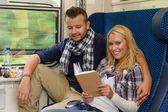 Coppia viaggia in treno donna lettura sorridente — Foto Stock