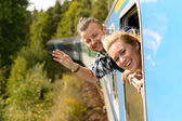 Couple waving with heads out train window — Stock Photo