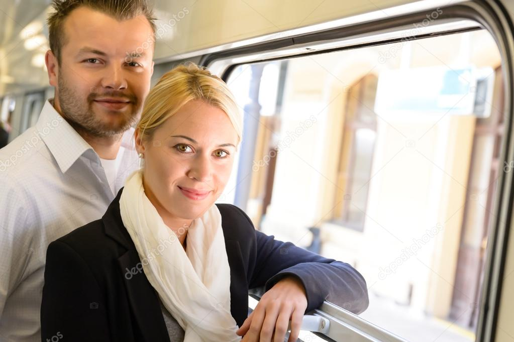 Woman and man standing by train window smiling commuters travel — Stock Photo #17417359