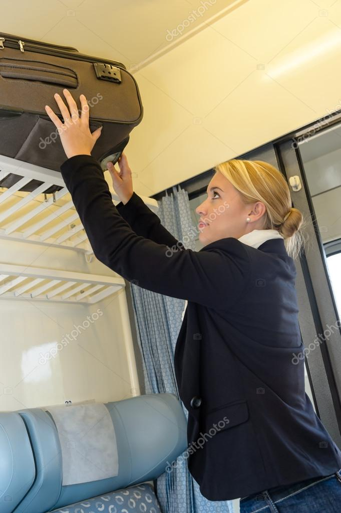 Woman putting her baggage on train grid compartment lifting commuter — Stock Photo #17417409
