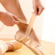 Постер, плакат: Ballet dancer tying slippers around her ankle