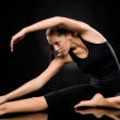 Young woman in separate leg stretching pose — ストック写真