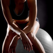 Thoughtful young woman relaxing on fitness ball — Stock Photo #18446401