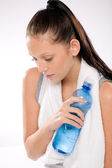 Woman thirsty after exercises holding water bottle — Stock Photo