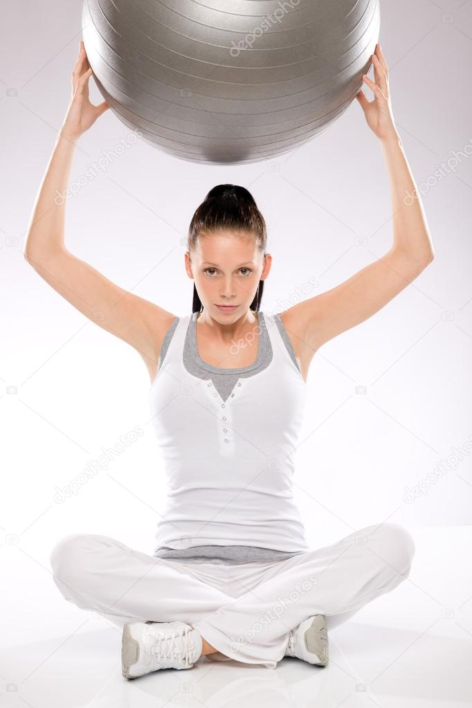 Young woman sitting and holding fitness ball above her head — Stock Photo #18446615