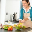 Happy woman making salad kitchen vegetables cooking — ストック写真