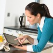 Young woman reading recipe tablet kitchen searching — ストック写真