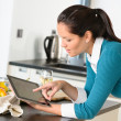 Young woman reading recipe tablet kitchen searching - Stock Photo