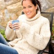 Smiling woman drinking tea patio sweater relaxing - Stok fotoraf