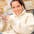 Smiling woman drinking hot cocoa relaxing garden - Foto Stock