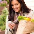 Smiling woman shopping vegetables mobile phone sms - Stock Photo