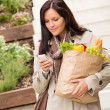 Young woman holding groceries vegetables shopping phone — Stock Photo #19055287