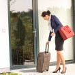 Businesswoman leaving house traveling carrying baggage hurried - Stock Photo