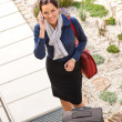 Pretty filght attendant leaving calling luggage phone — Stock Photo