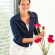 Young woman arranging flowers dinner table — Stock Photo #19055391