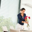 Smiling woman putting red roses dinner room — Stock Photo
