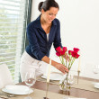 Young woman placing flowers dinner table - Stock Photo