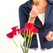 Woman setting table romantic dinner roses Valentine's - Stockfoto