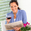 Foto Stock: Cheerful woman reading drinking wine newspaper living
