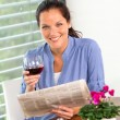 Cheerful woman reading drinking wine newspaper living — ストック写真