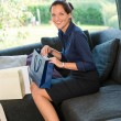 Young smiling woman sitting shopping bags couch — ストック写真