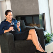 Happy woman relaxing armchair text messaging wine - Stock Photo