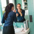 Smiling woman bathroom applying lipstick mirror businesswoman — Stockfoto #19055625