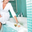 Smiling woman relaxing wrapped towel bathroom bathtub - Photo